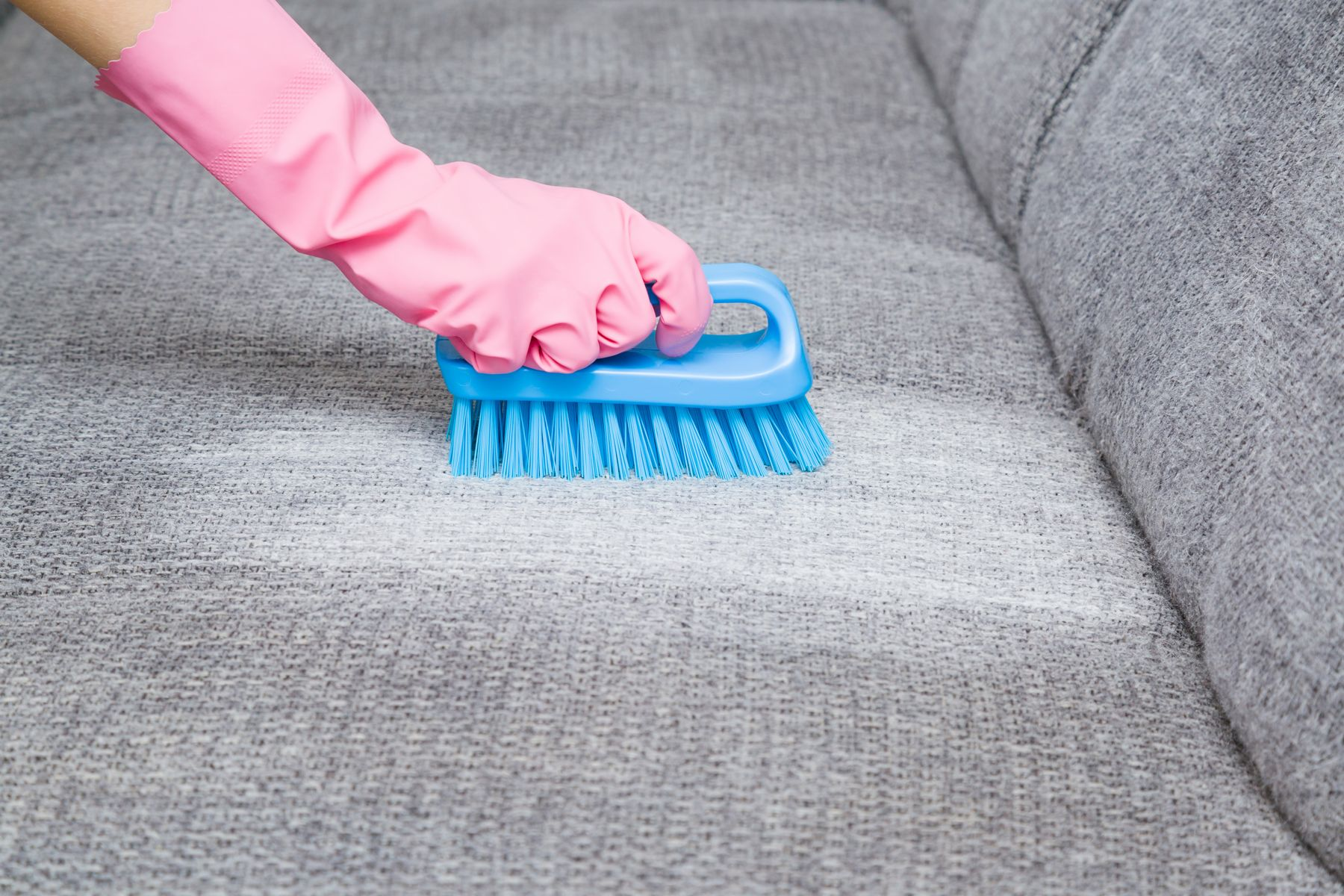 person wearing a pink glove cleaning a grey sofa with a blue brush