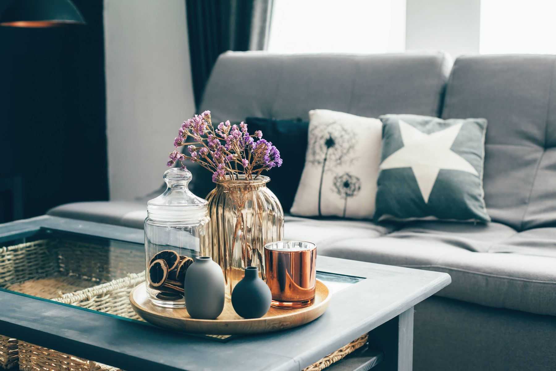 living room with gray sofa, pillows and decorative objects