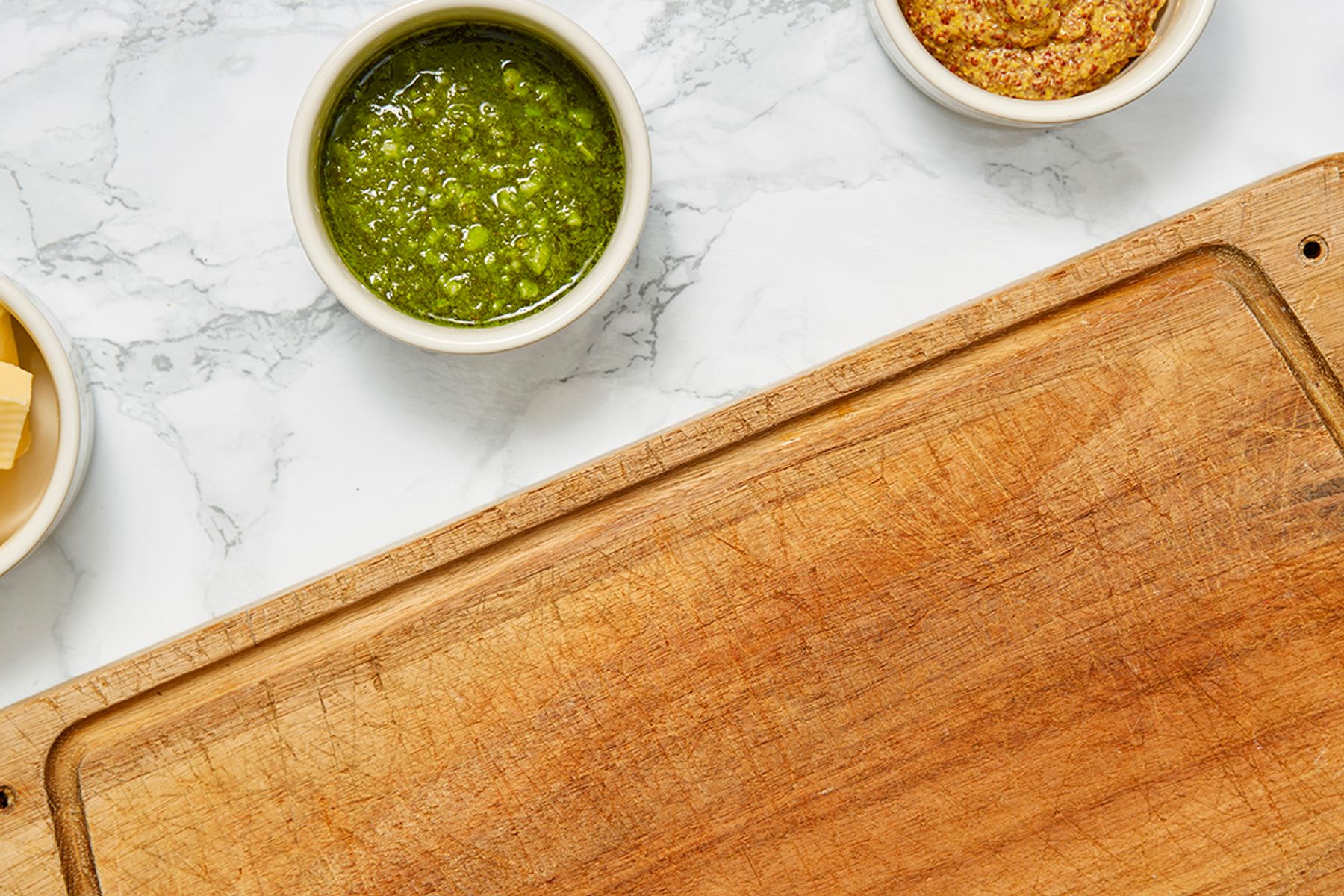 wooden chopping board next to three little bowls on a marble surface