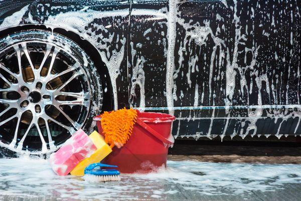 Carro ensaboado, balde, esponjas, e escova de limpeza