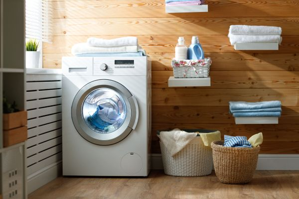 lavarropas con toallas blancas encima y dos canastos con ropa al lado