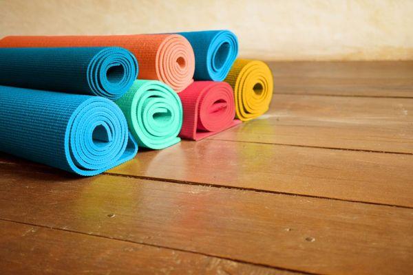 kleurrijke yogamatten gewikkeld rond houten vloer