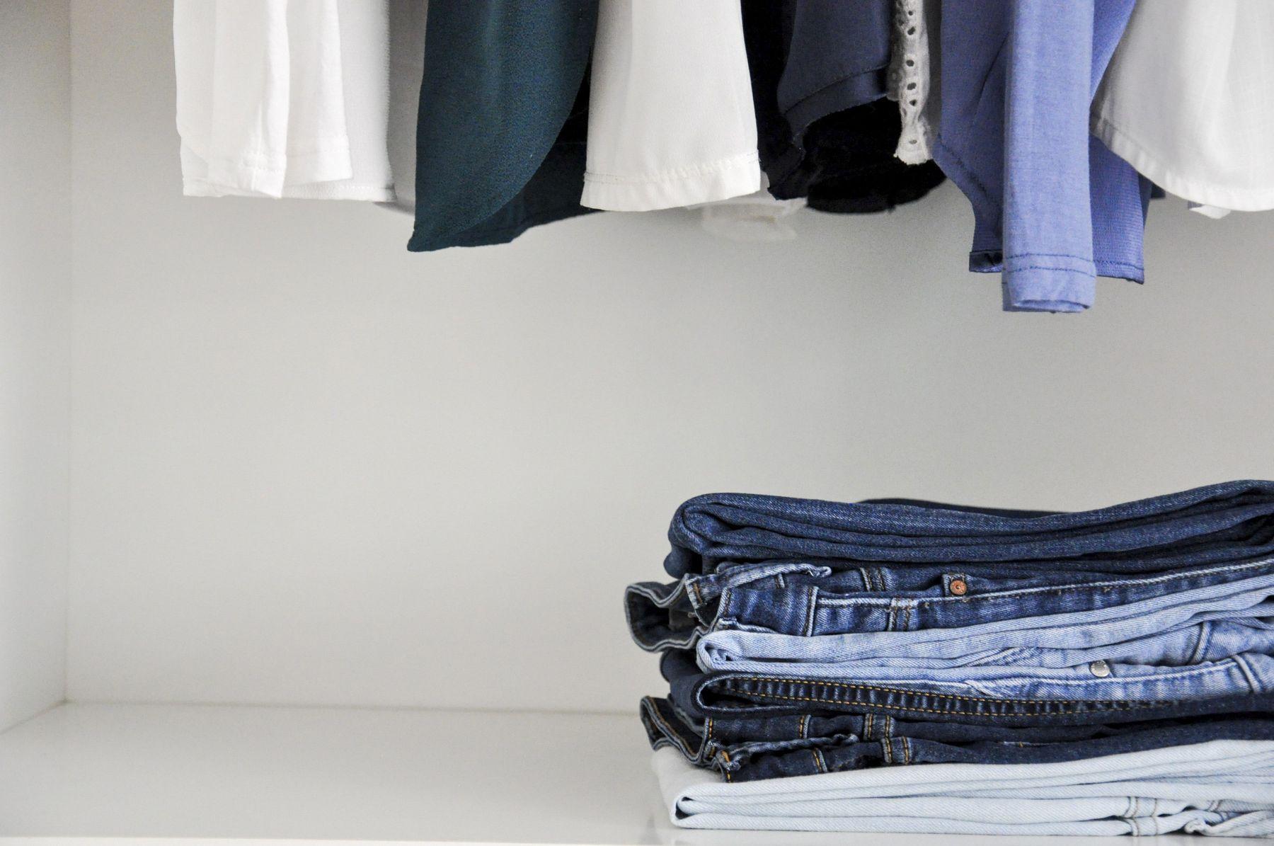 Pilha de calças jeans na prateleira abaixo das camisas penduradas no armário