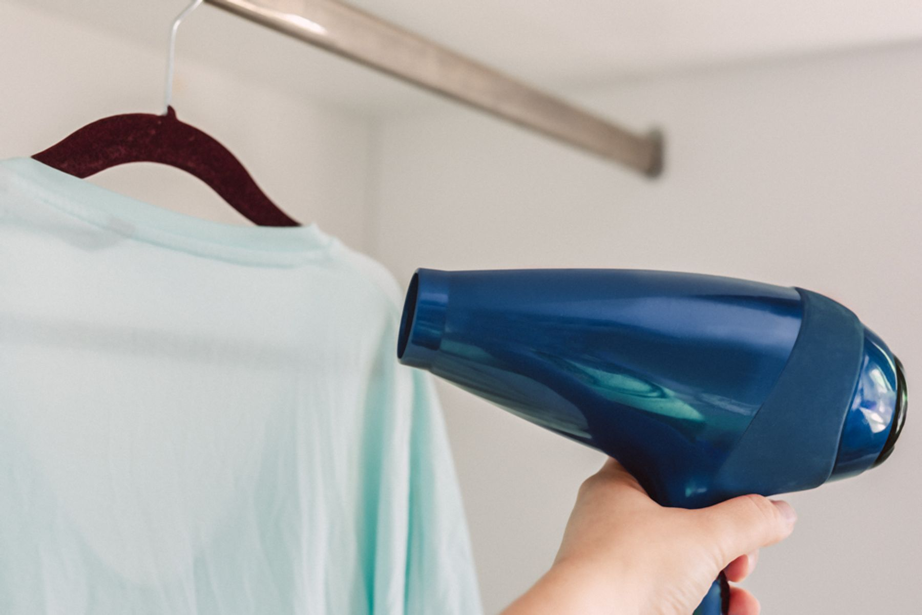 Using a hairdryer to dry a top hanging on a hanger