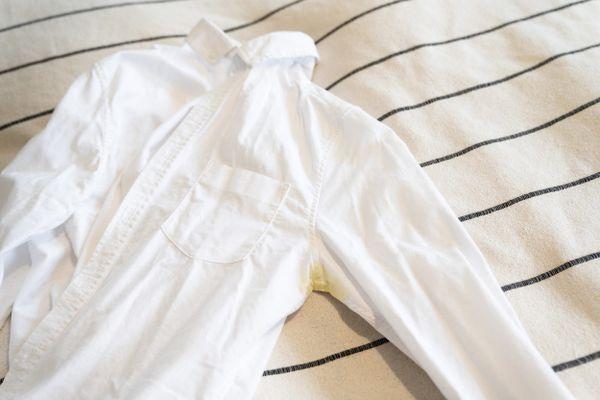 Camisa branca com amarelado na axila em cima da cama