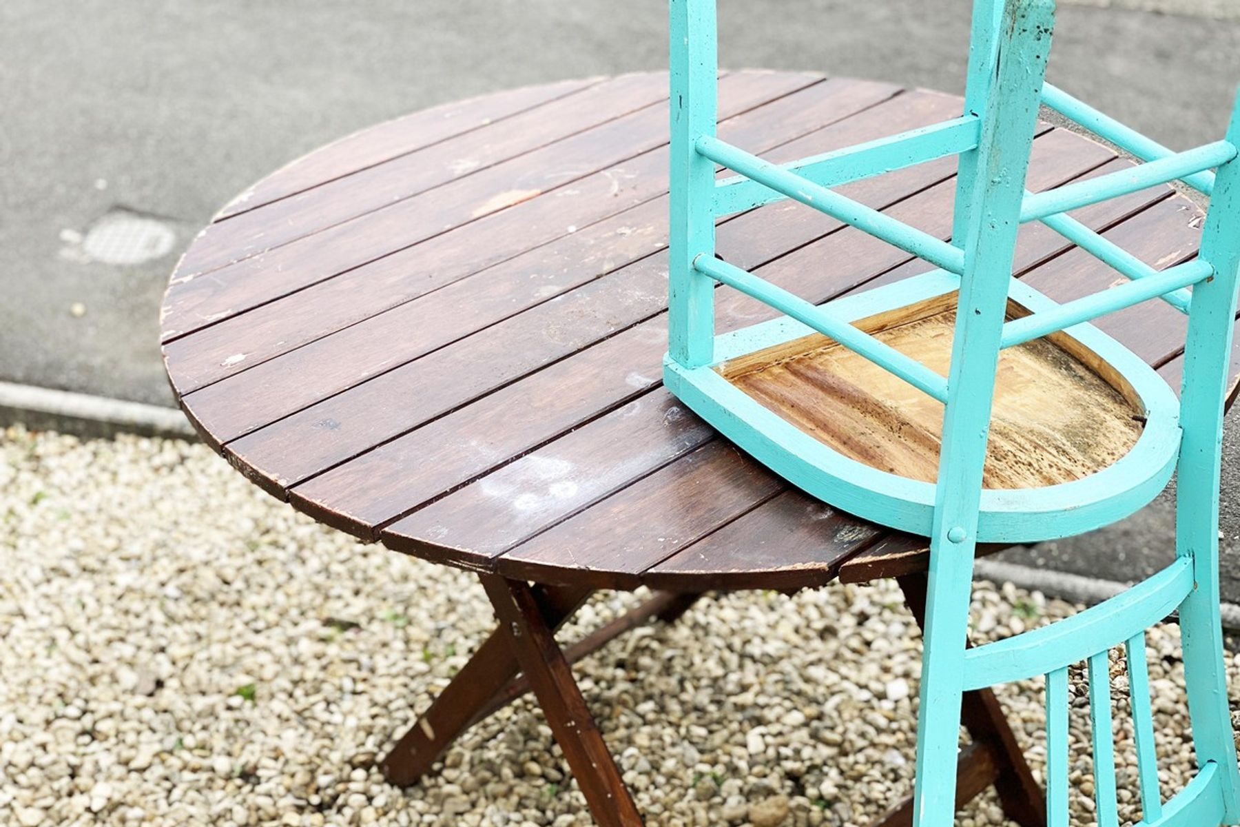 A blue wood chair upturned on top of an old wooden table