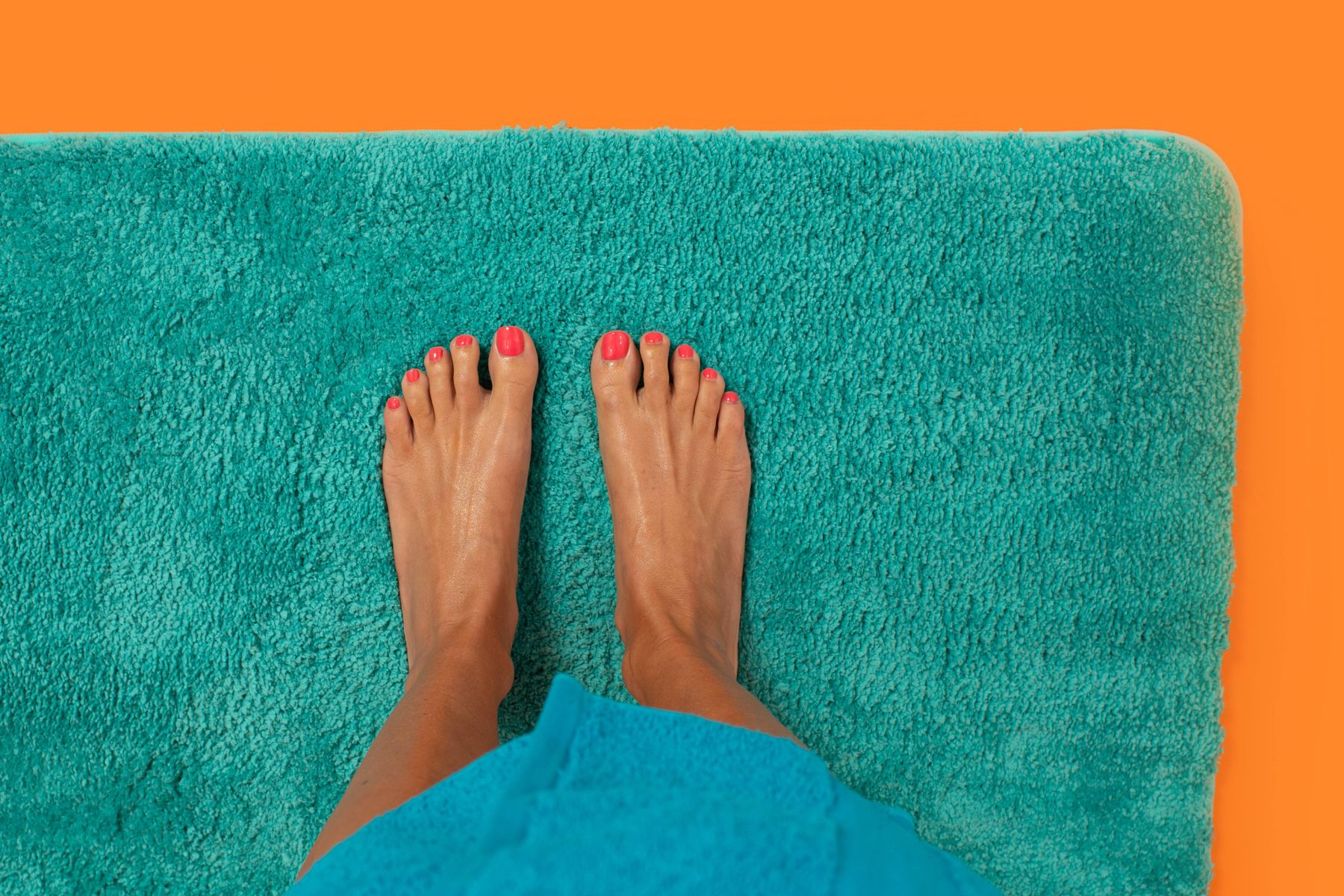 female feet on the blue bathroom rug