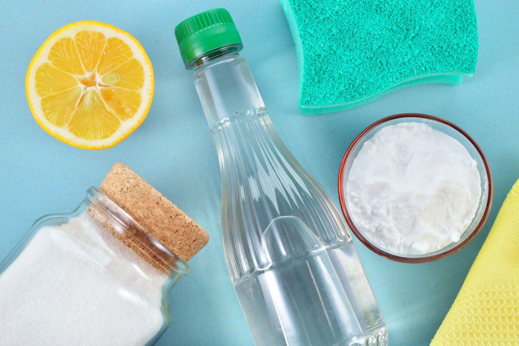 bottle of vinegar, baking soda, a lemon slice and green sponge on blue table