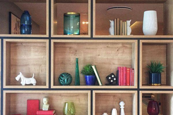 Holzregal mit Ornamenten und Büchern
