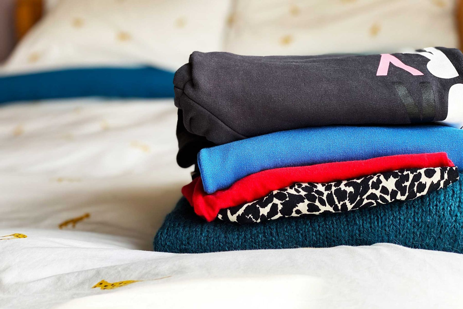 Colourful folded clothing on a bed