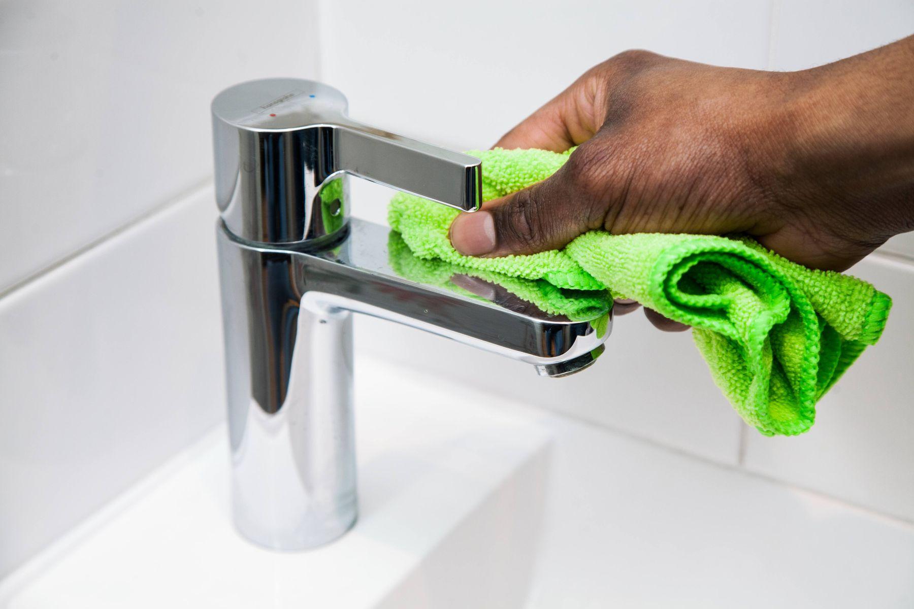 Pessoa limpando torneira do banheiro com pano