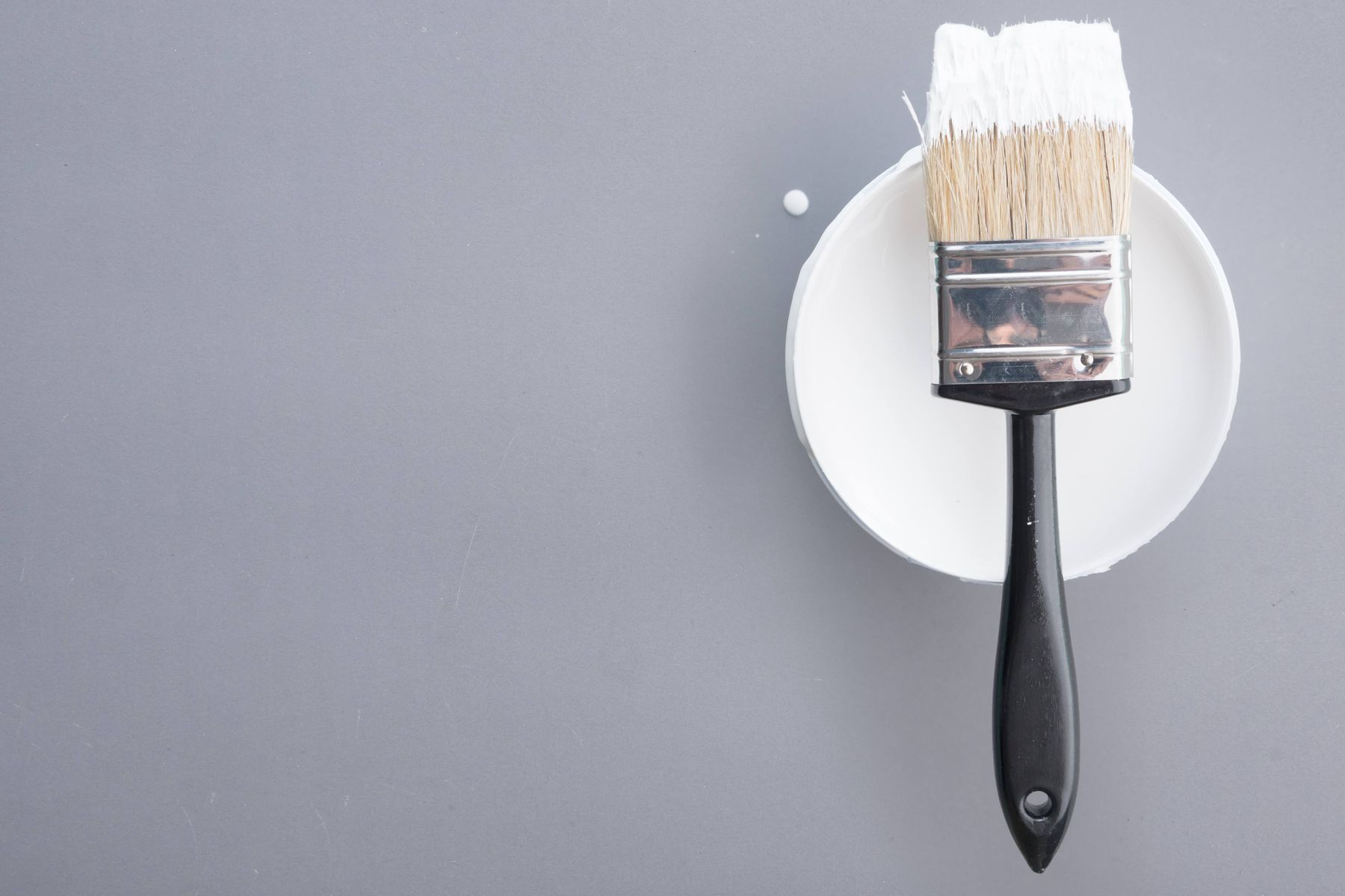 Paint brush leaning on a tin of white paint for repairing cracks in the ceiling