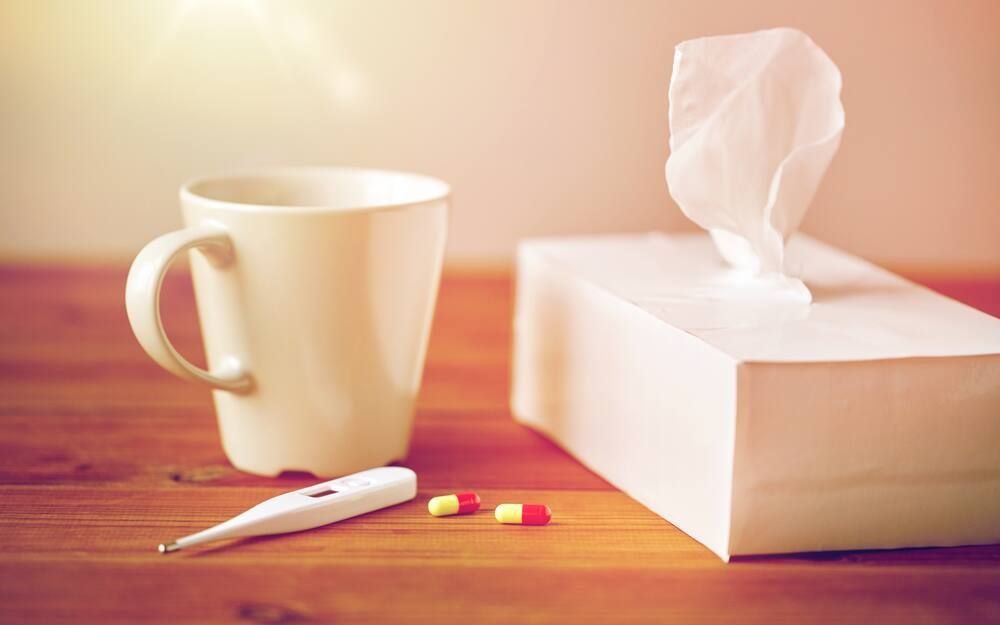 Mug of tea with medicine and tissues