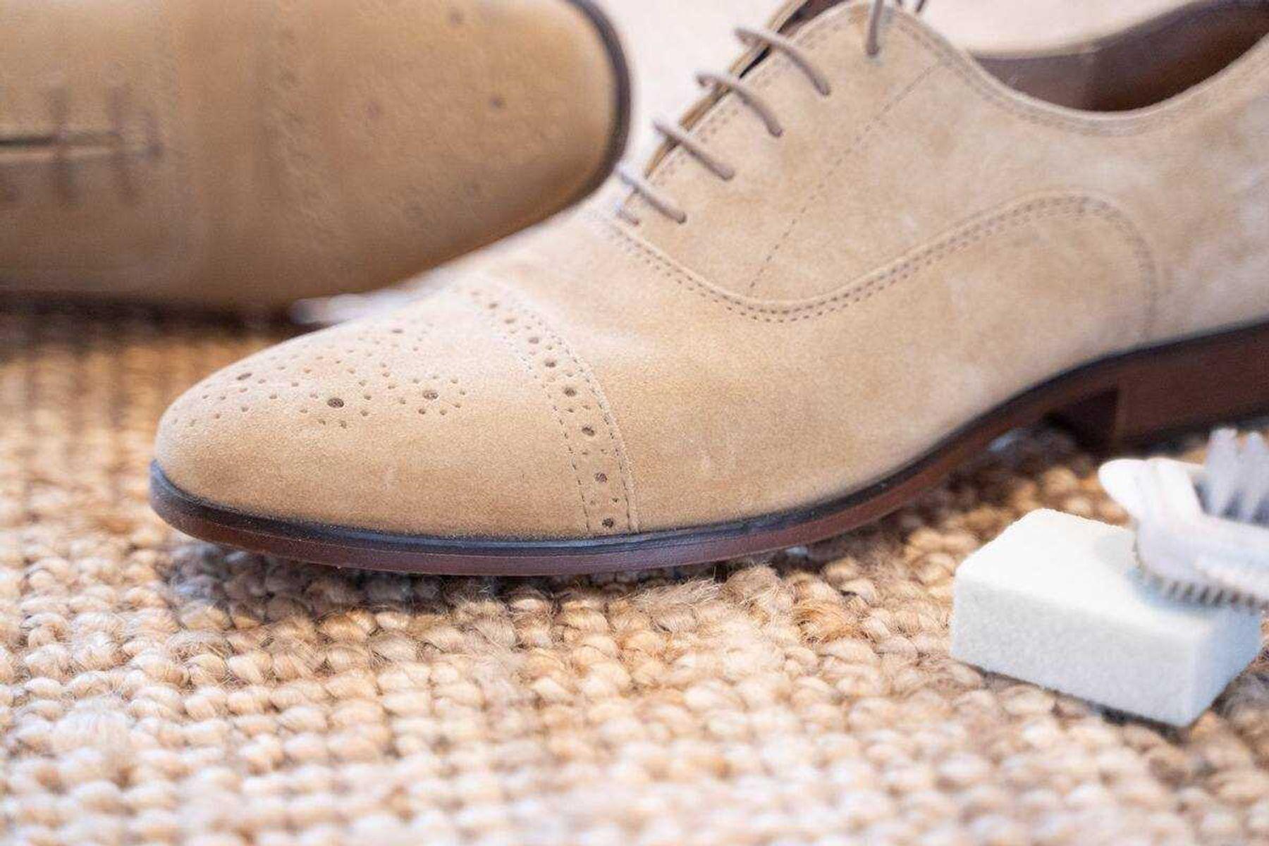 close em sapato de camurça marrom sob superfície marrom