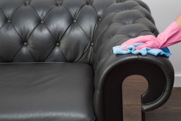 A person's hand cleaning faux leather sofa