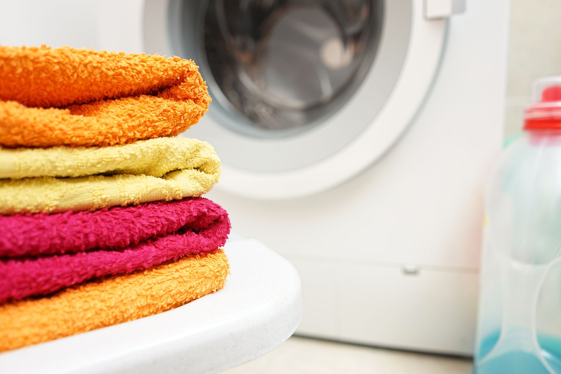 A pile of orange, yellow, and red towels in front of a washing machine