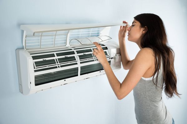 a woman opening an air conditioning unit