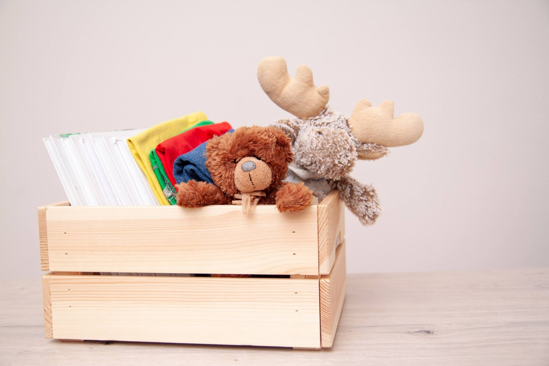 toys and books in a wooden box
