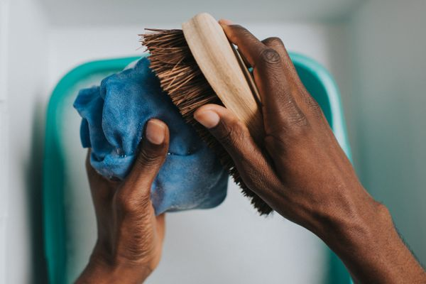 Close up of hands hand-washing clothes with a brush