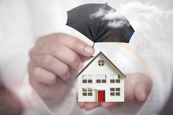 Mãos segurando uma miniatura de casa branca com porta vermelha com um guarda-chuva preto