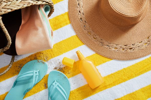 beach-hat-sunscreen-flip-flops-and-bag-on-a-beach-towel
