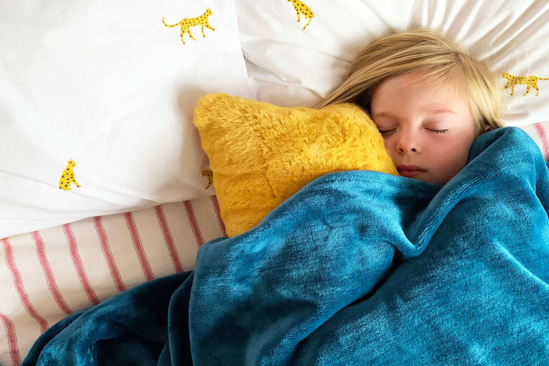 child sleeping in a cozy bed