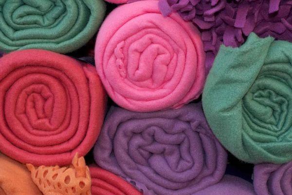 Muchas frazadas de polar de distintos colores enrolladas