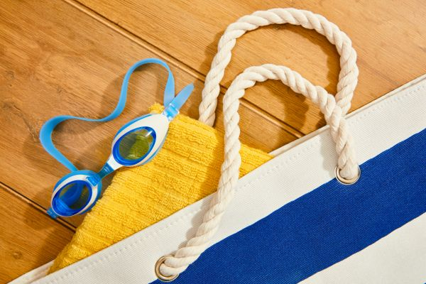 mildew odours: blue and white beach bag containing yellow towel and blue swimming goggles