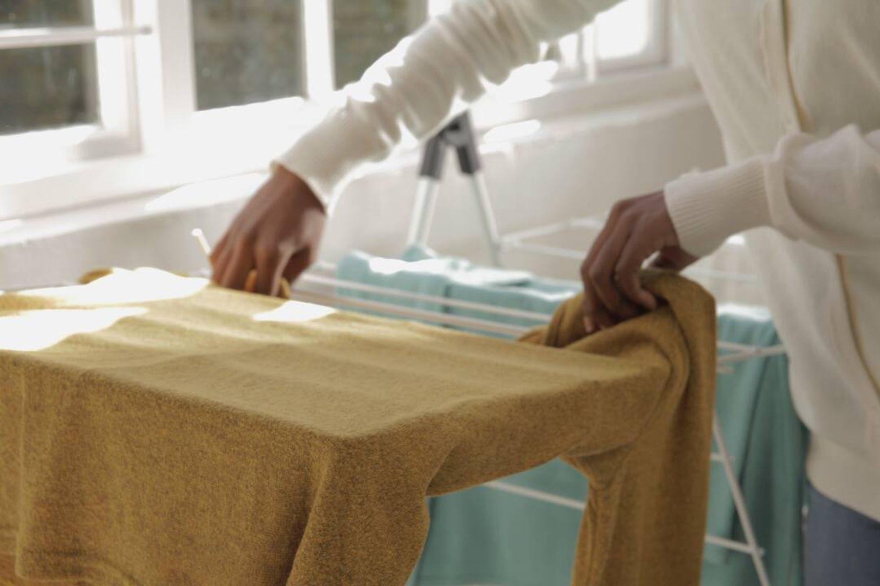 Pessoa colando roupas para secar no varal de chão para tirar o mofo da roupa