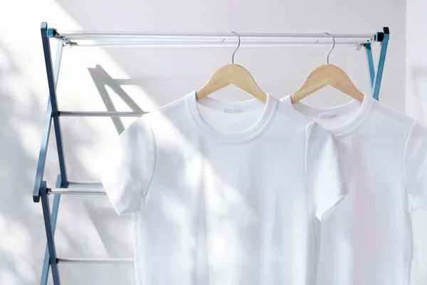 freshly cleaned white t-shirts on a drying rack