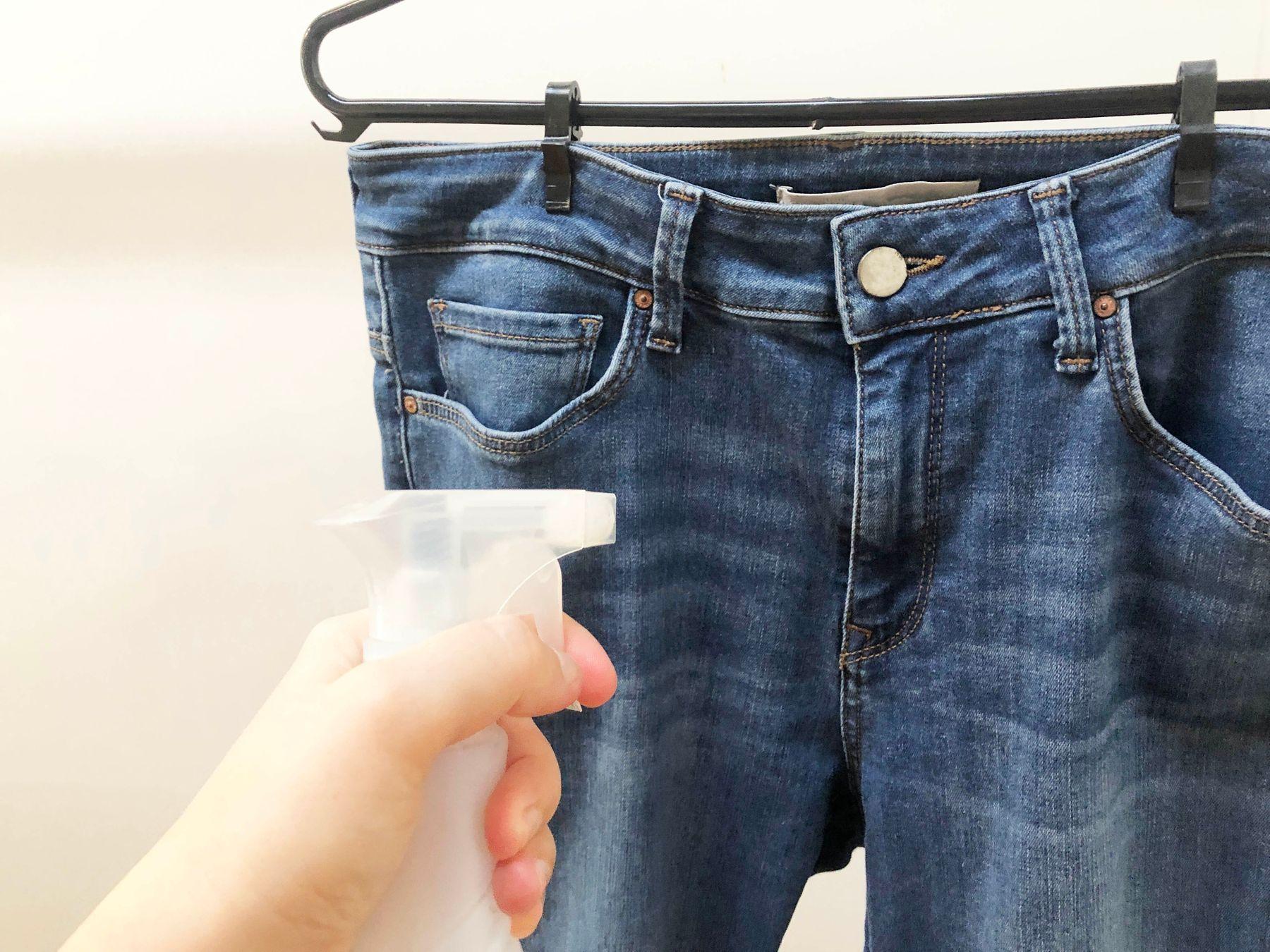 Calça jeans no cabide e mão que segura um aspersor