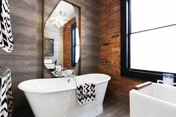 Nhà vệ sinh hiện đại với tường gạch đỏ và gương soi lớn