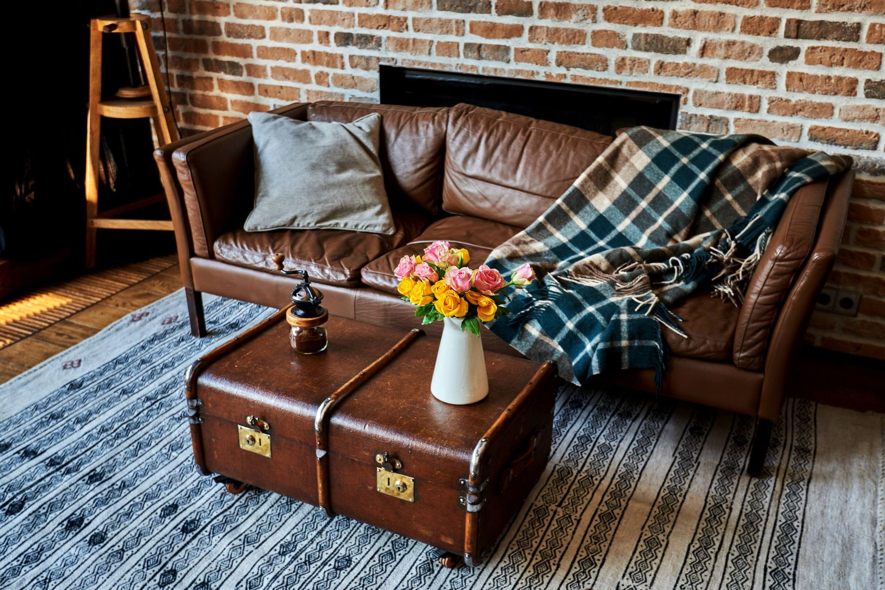 cozy living room with leather sofa and plaid blanket