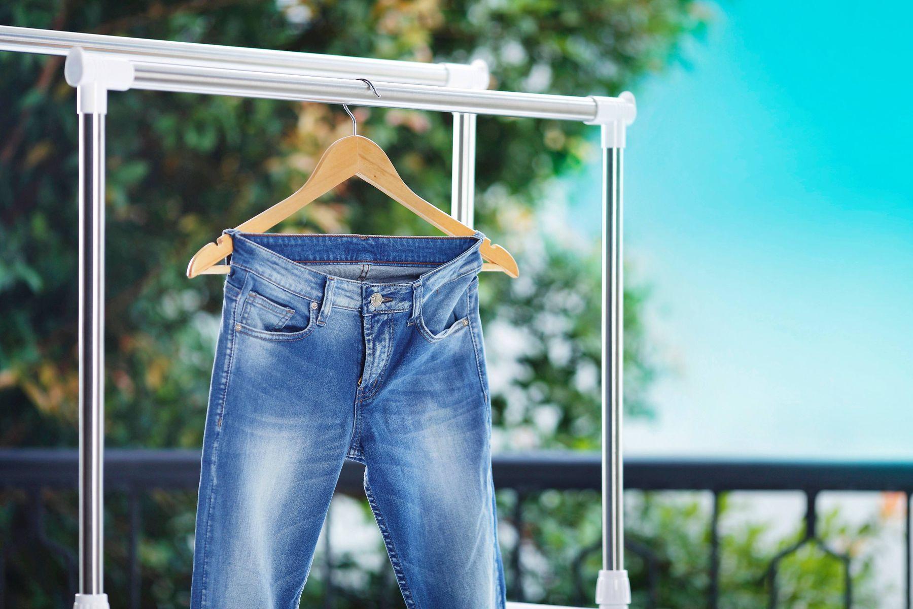 Jeans hängen von einem Kleiderbügel im Garten