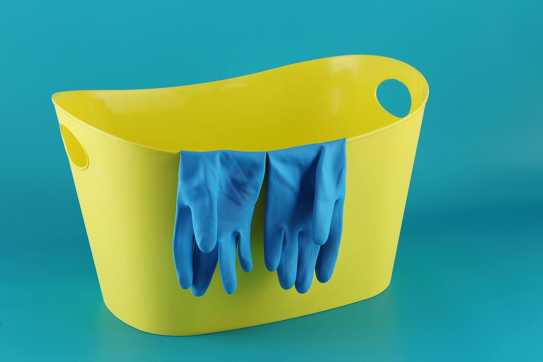 Luvas azuis de borracha em cima de balde de plástico amarelo e parede com fundo azul