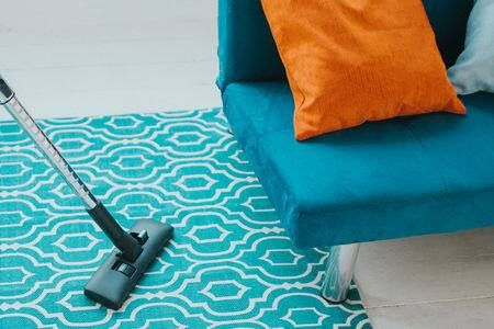 Almofada laranja sobre o sofá azul e tapete verde e branco sendo aspirado