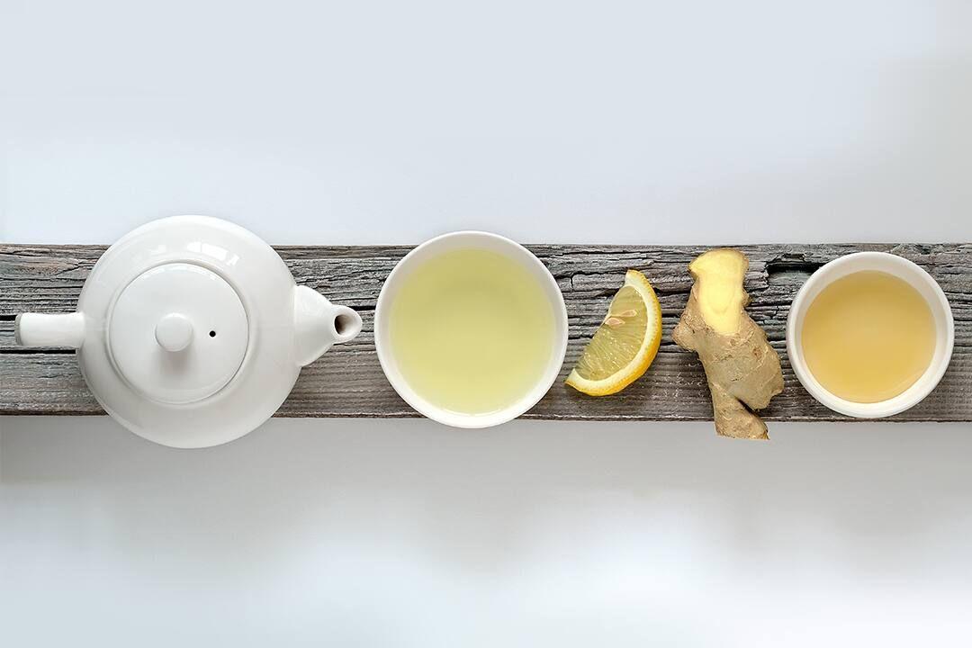 Bule e xícara branca sobre tábua de madeira com limão e gengibre