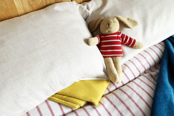 Coelho de pelúcia deitado sobre os travesseiros de uma cama arrumada