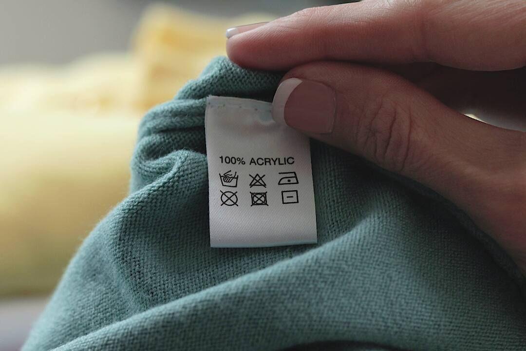 Pessoa segurando a etiqueta com os símbolos de lavagem
