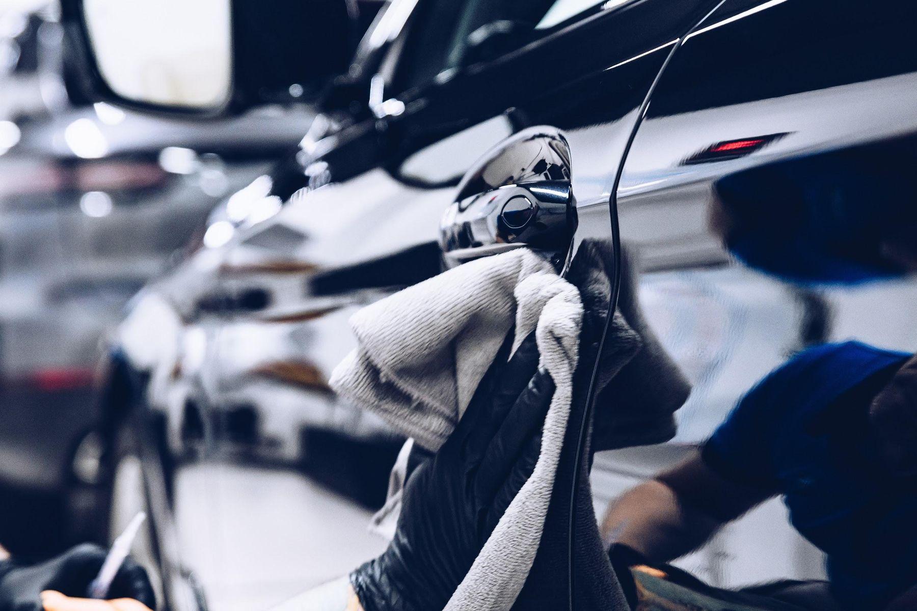 Mão passa pano de polimento na lataria de um carro