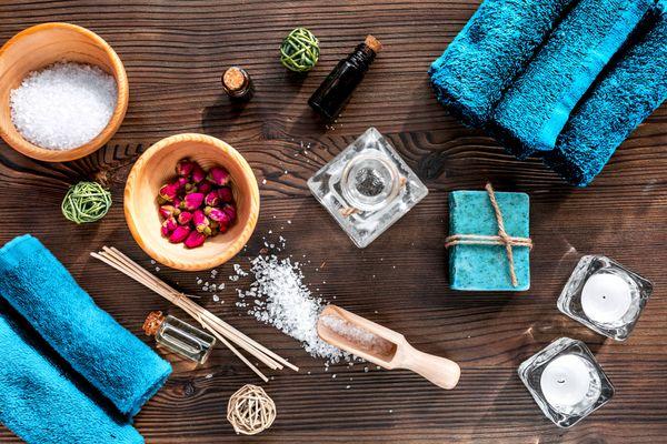 Kerzen, Salze, Öle, Blumen und blaue Tücher auf Holztisch