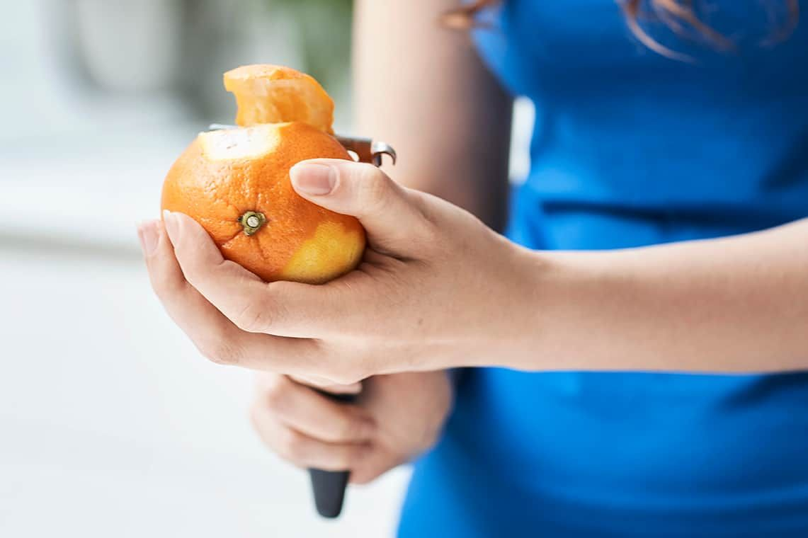 Woman's hand peeling orange