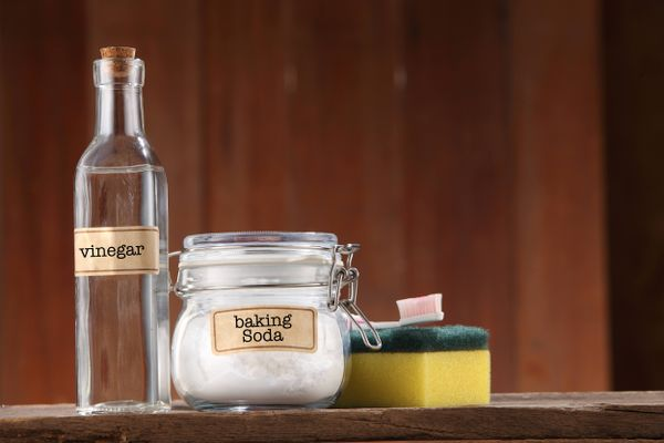 Productos de limpieza natural: vinagre, bicarbonato, esponja y cepillo.