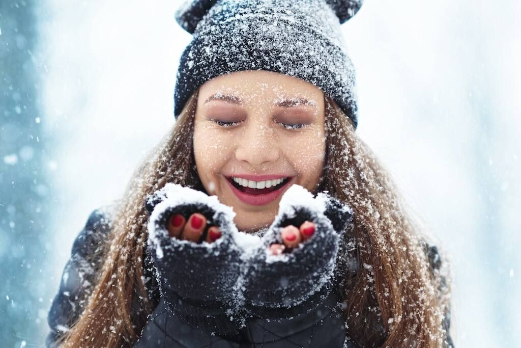 close-up of fresh-faced woman outside playing with snow for winter skin care tips