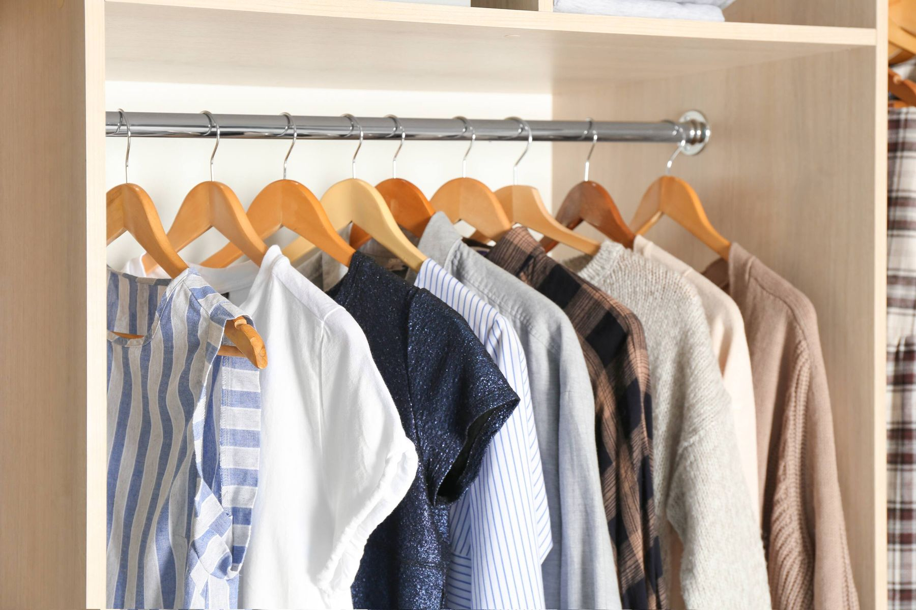 clothes hanging on hangers in wardrobe
