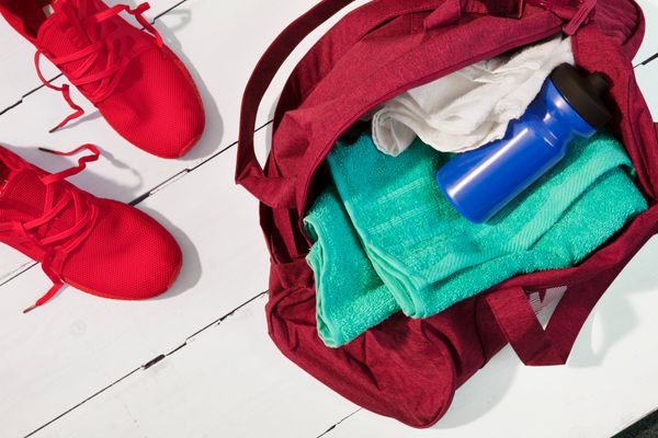 A red gym bag with towel, water bottle, trainers clothes with a sweat smell