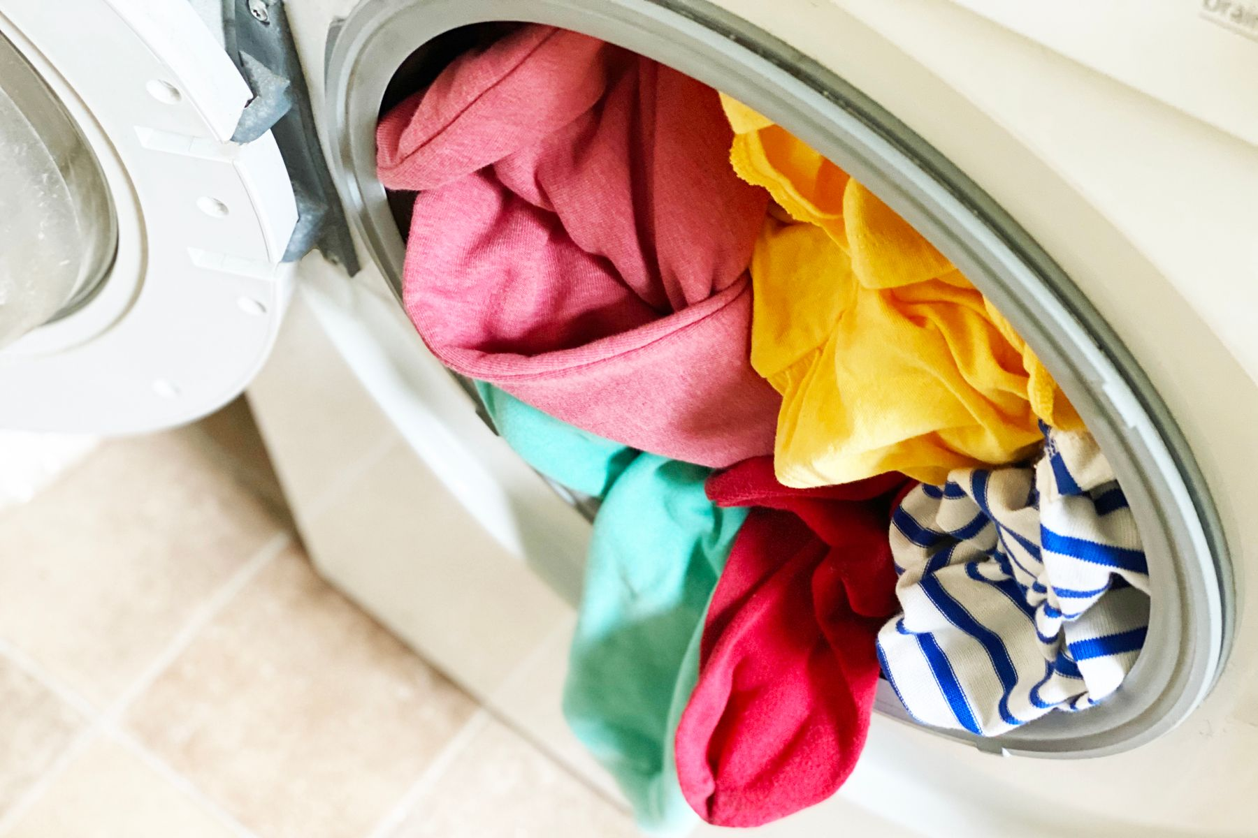A washing machine with colourful clothing spilling out of it