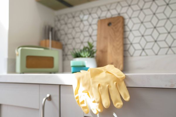 yellow rubber gloves and wooden board on the kitchen countertop