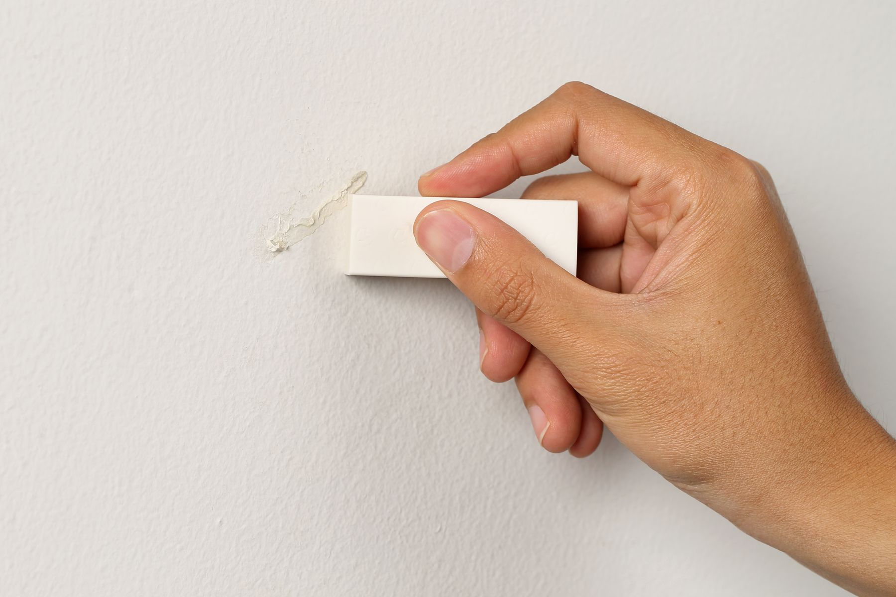 Step 2: Wiping sticker residue from a wall with an eraser