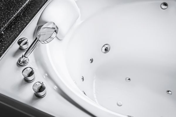 A white jacuzzi with gleaming silver tap and filters